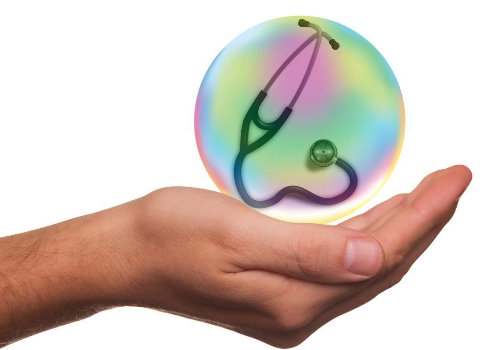 手のひらの上で聴診器を包んだ球体を持っている画像