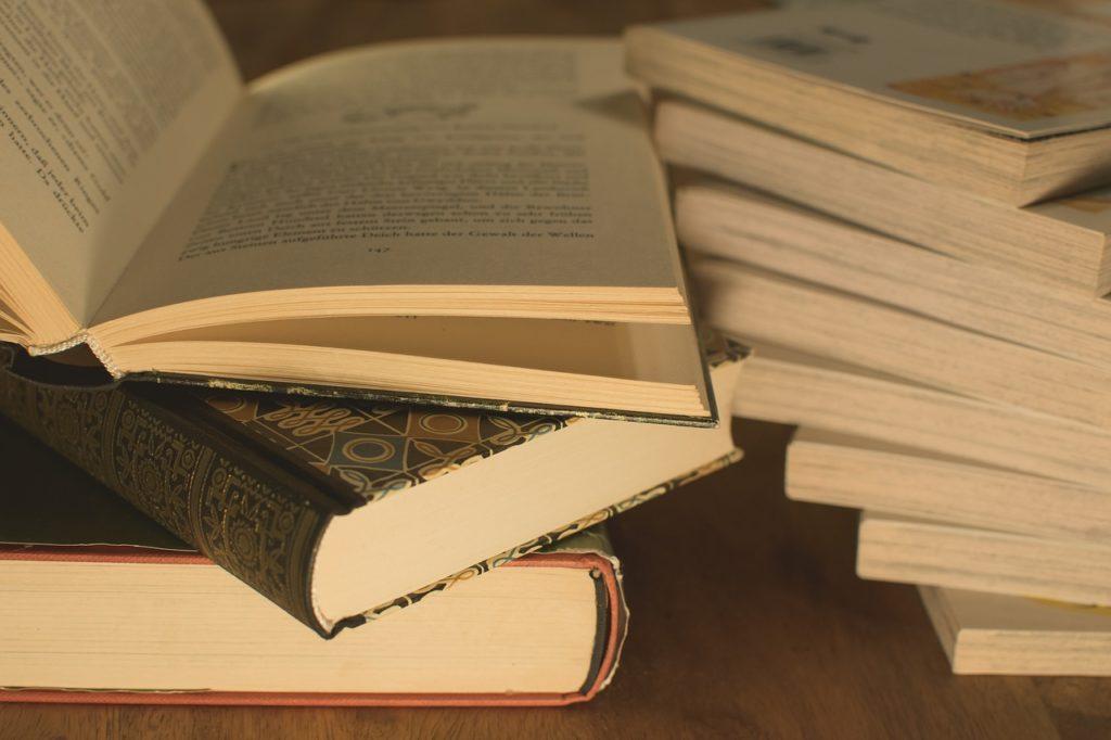 厚めの本が重なっていて一番上の本は開かれている