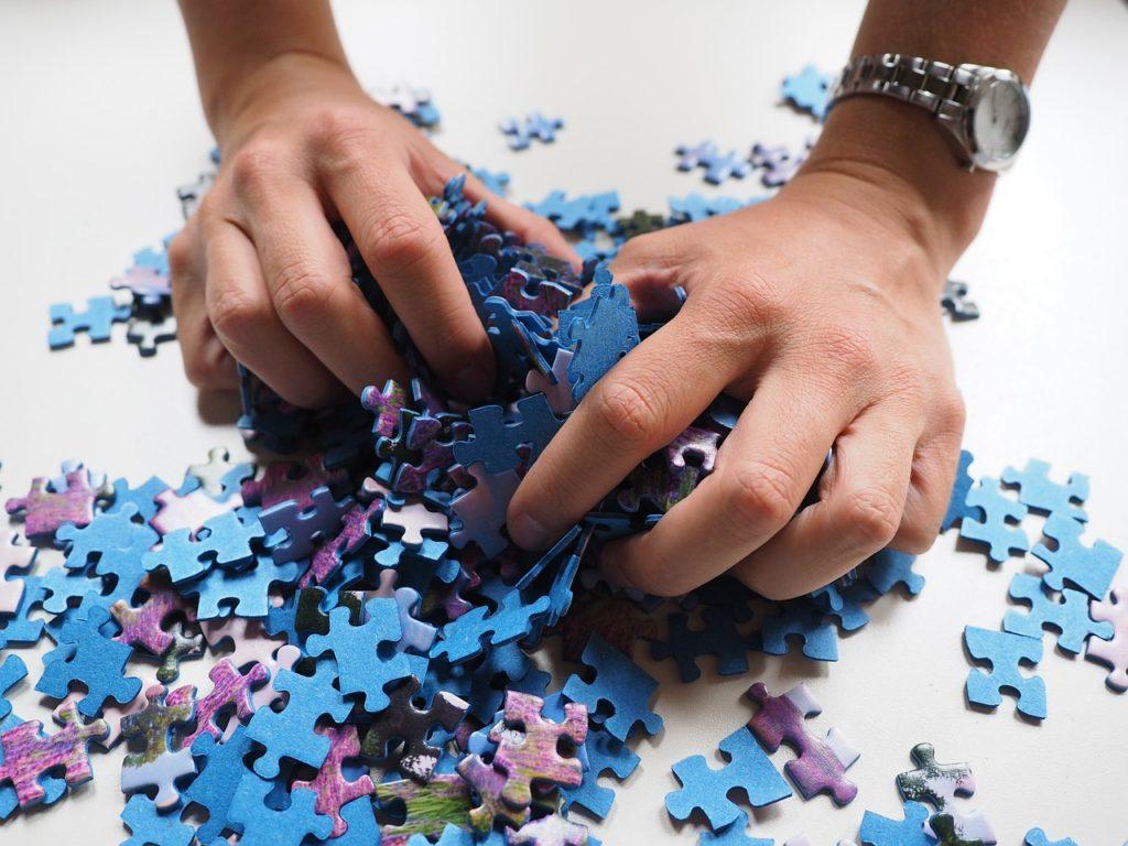 ジグソーパズルを両手で混ぜている画像