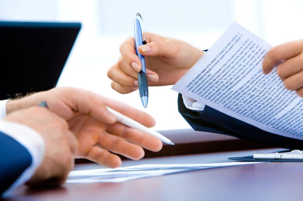 二人がペンを持っており書類を使ってやりとりしている手元の描写