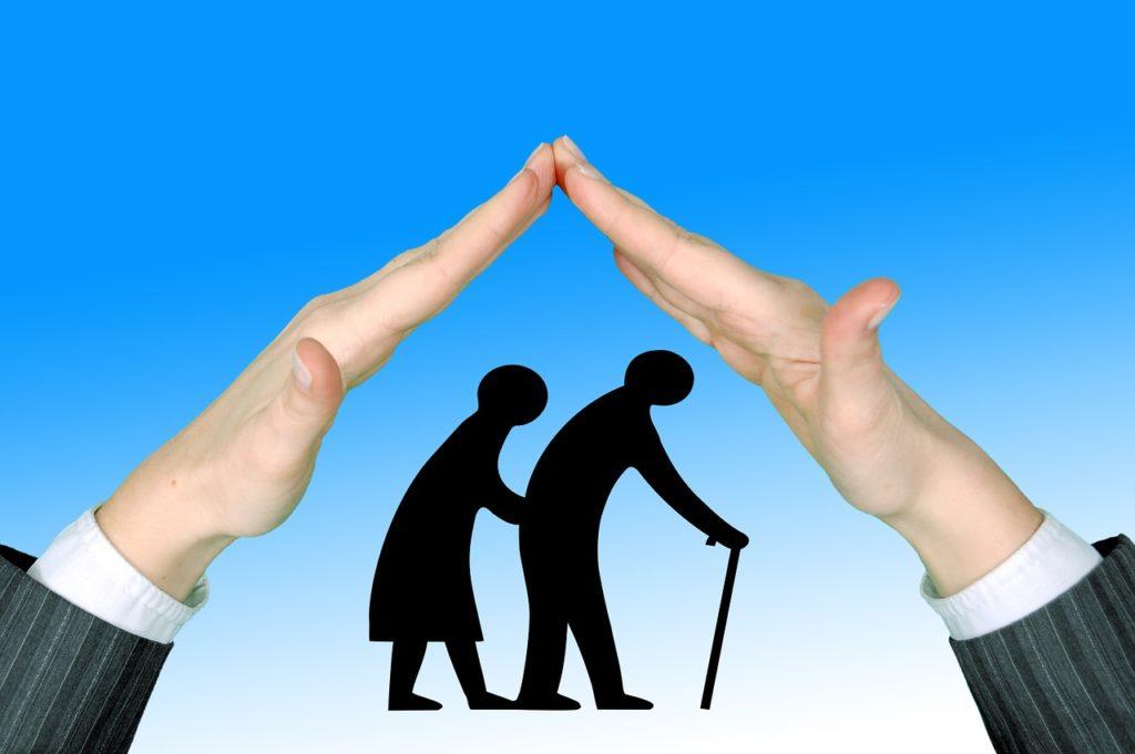 両手で山を作り、その山の中に歩く老夫婦のシルエットがある