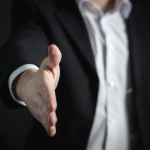 右手を差し伸べ握手を求めるビジネスマン